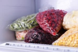 close up of bags of frozen produce on a freezer shelf - cranberries, corn, greens etc